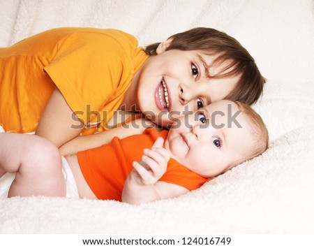 Older happy laughing brother holding cute baby sister lying on fur blanket, studio shot - stock photo