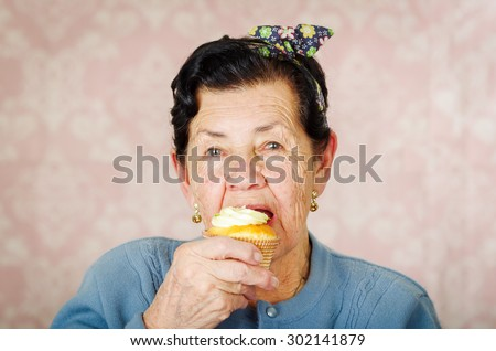 Older hispanic happy woman wearing blue sweater sitting in front of camera having a bite off cupcake. - stock photo
