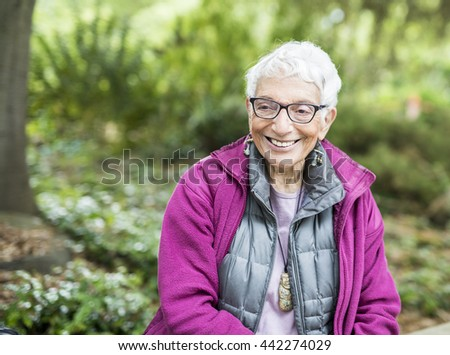 Older Independent Woman Sitting in Park Happy and Smiling. Wearing warm clothes. - stock photo