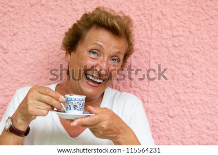 Older lady drinking her Turkish Coffee and giving caffeinated look. - stock photo
