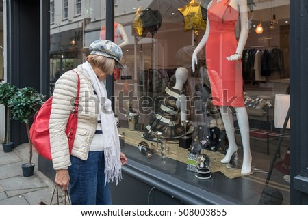 Older lady stops to look at a dress in a window in Carmarthen, Wales