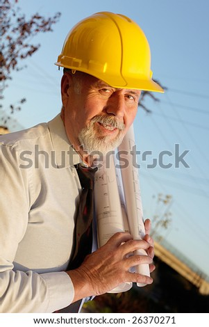 Older male engineer with construction blueprints