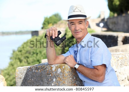 Older male tourist with binoculars leaning on the citadel walls at Blaye in SW France - stock photo
