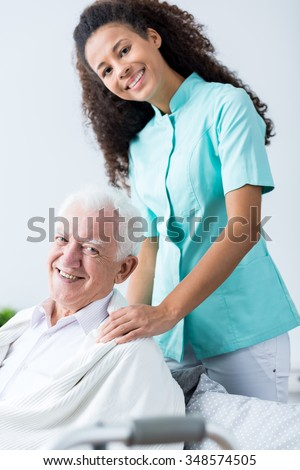 Older man and his carer at home - stock photo