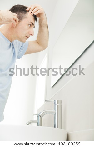 older man checking hairloss in bathroom mirror - stock photo