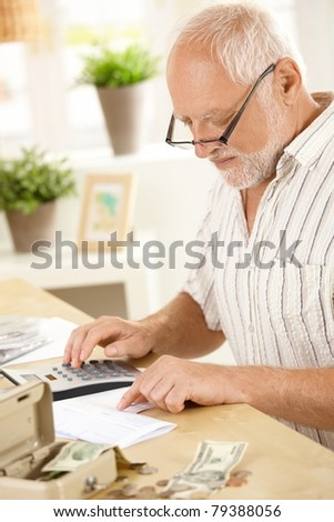 Older man concentrating on financial job, using calculator at home.?