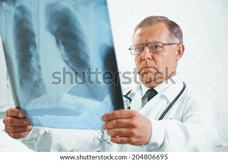 Older man doctor examines x-ray image of lungs in a clinic - stock photo