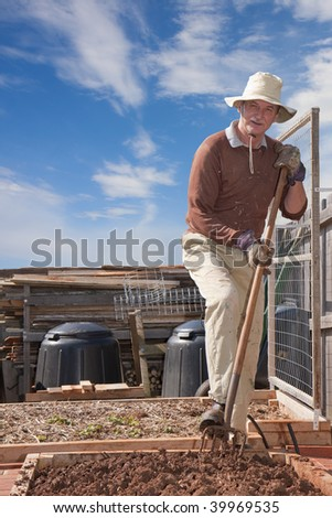 Older man gardening with pitchfork in garden bed - stock photo