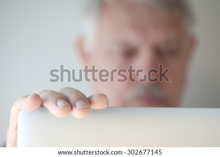 Older man has hand on his laptop, face defocused - stock photo