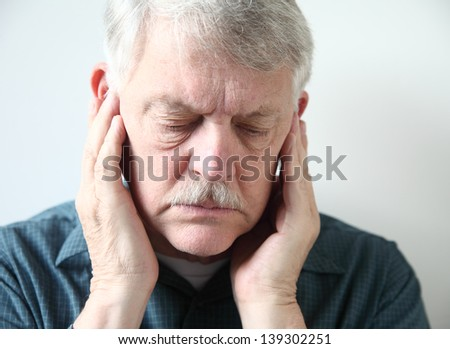 older man holds both hands to his upper jaw near the ears - stock photo