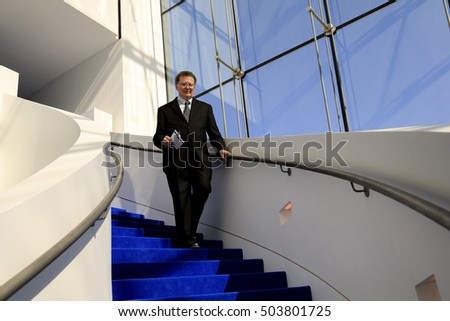 Older man in a suit coming down the stairs