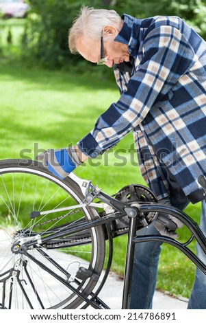 Older man in glasses repaired pedals a bicycle