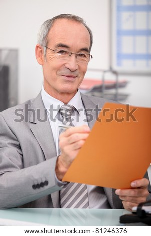 Older man making notes in a file