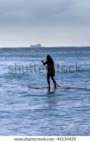 Older man paddle boards across Waikiki Bay while ship is leaving port.  Evening light silhouettes paddler. - stock photo