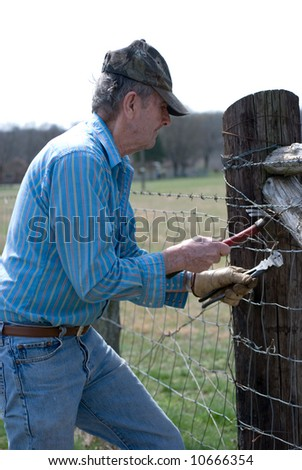 Older man repairing a  broken fence with a hammer and fence pliers - stock photo