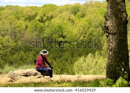Older man resting on a bluff top enjoying the view; Missouri state parks - stock photo