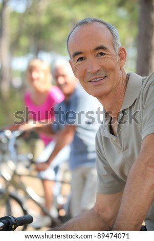 Older man riding a bike in the forest with friends - stock photo
