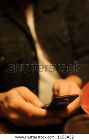 Older man's hands texting someone with his cell phone. - stock photo