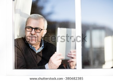 Older Man sitting at the window with his tablet and relaxing in the sun - stock photo