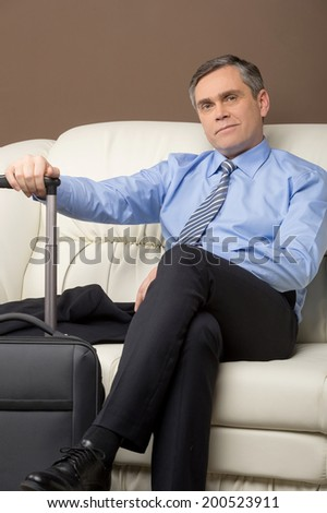 older man sitting on couch with luggage. man resting on sofa prepared to leave