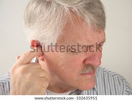 older man tries to relieve the pain deep in his ear - stock photo
