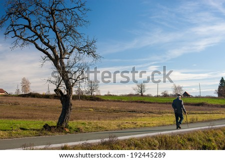 Older man walking through the country road in autumn. - stock photo