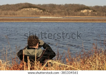 Older man watching white pelicans across the lake - stock photo