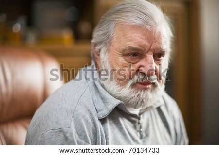 Older man with black eye, beard and white hair, serious expression - stock photo