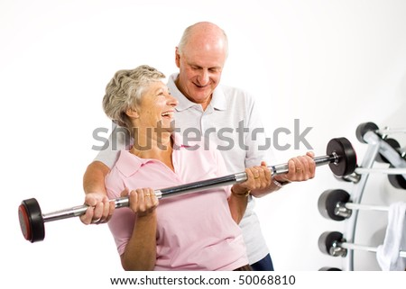 Older mature couple lifting weights in the gym - stock photo