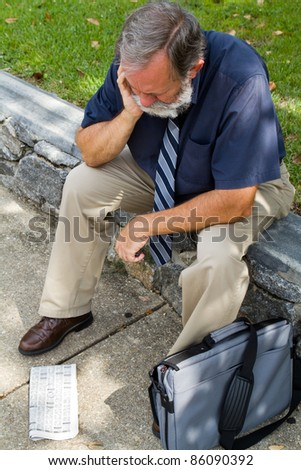 Older mature unemployed office worker sits distressed after viewing the want ads for a job. - stock photo