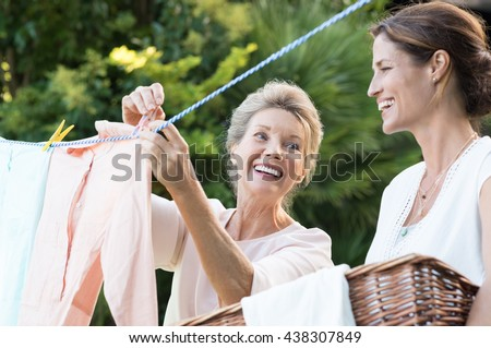 Older mother and young daughter hanging clothes outdoor to dry. Smiling daughter helping mother with laundry. Cheerful mother and daughter in conversation while hanging clothes outside. - stock photo