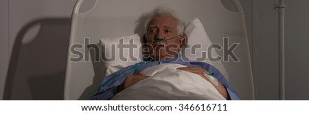 Older patient lying in bed and feeling lonely in hospital - stock photo