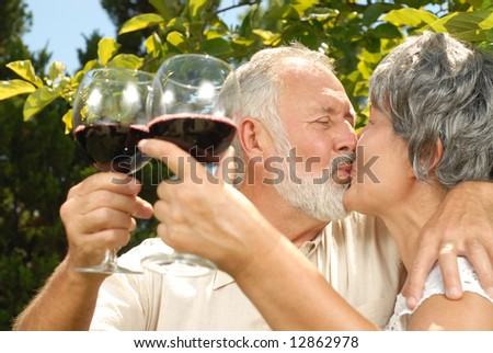 Older people kissing in the garden while on a wine tasting - stock photo