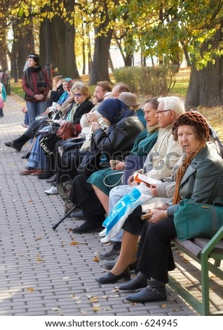 Older persons prefer quiet rest in city park - stock photo