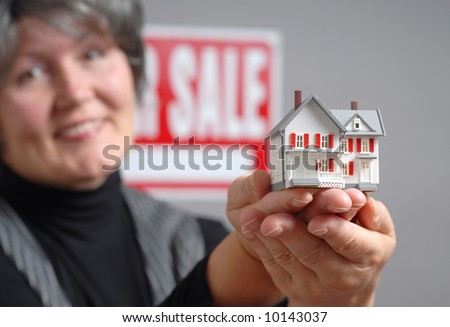 Older real estate agent with a house model for sale - stock photo