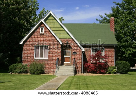 Older red brick house with green lawn and trees - stock photo