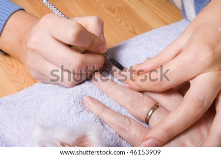 Older senior woman with arthritic hands receiving home spa treatment / manicure.