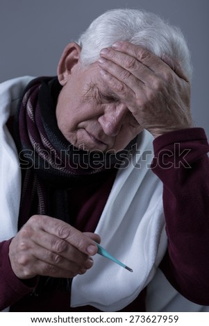 Older sick man with high fever and headache - stock photo