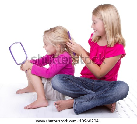 Older sister doing or combing younger sisters hair, white background - stock photo
