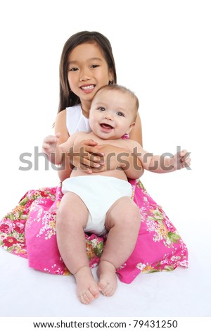 Older sister holding cute baby brother  over white background - stock photo