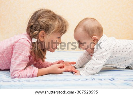 Older sister holding hands of her little sibling. Children lying on their tummies on the bed. Both laughing and having fun together. Side view. - stock photo