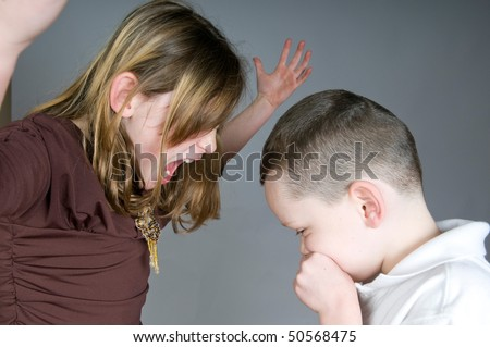 Older sister yelling at younger brother - stock photo