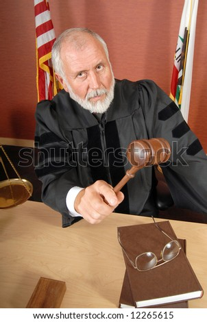 Older, stern and serious judge in his courtroom - stock photo