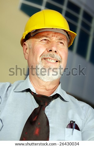 Older, successful engineer smiling as he is looking off toward his right