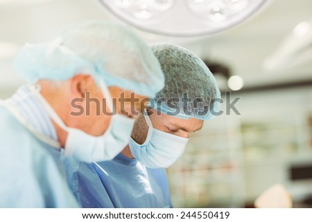 Older surgeon teaching new surgeon how to operate at the university - stock photo