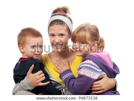 Older teen sister holding much younger brother and sister isolated on white. - stock photo