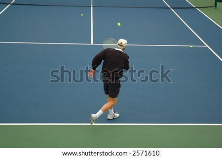 Older tennis player hitting ball