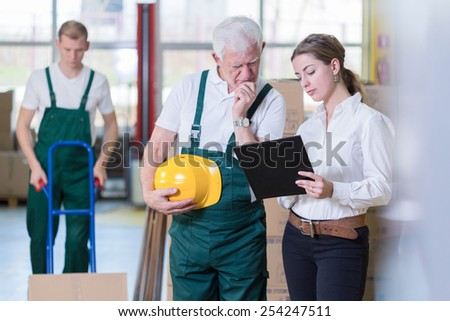Older warehouse employee and his young boss - stock photo