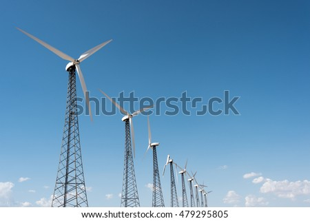 Older windmills in line - One is broken
