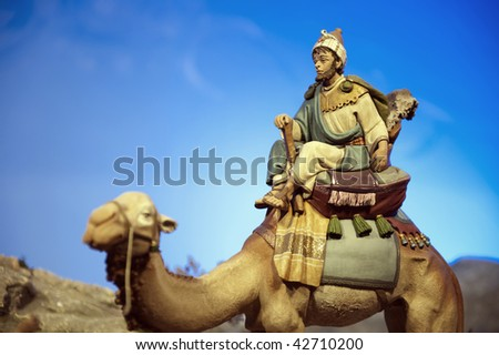 Older wise king with dromedary against blue sky. - stock photo
